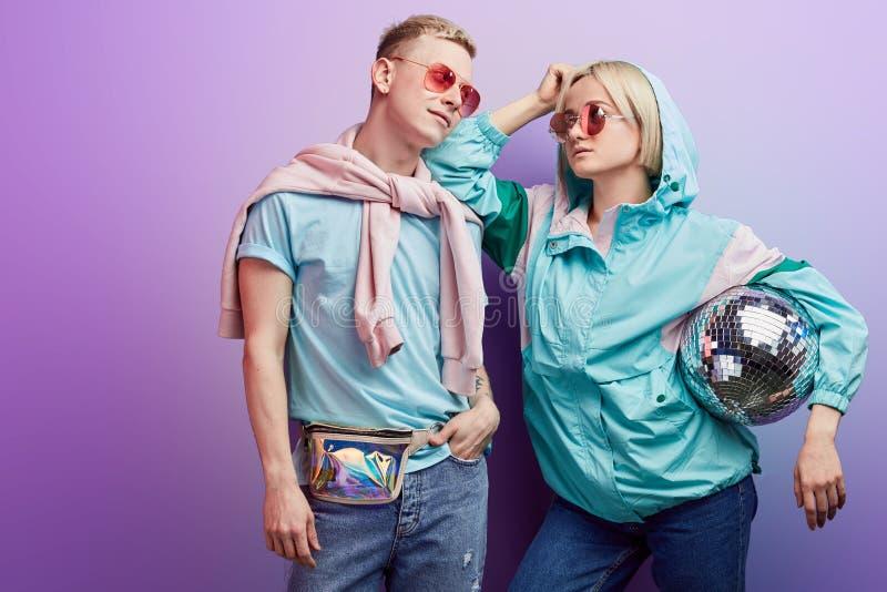 Jeunes couples ? la mode des danseurs posant avec la boule de disco sur le fond violet images libres de droits