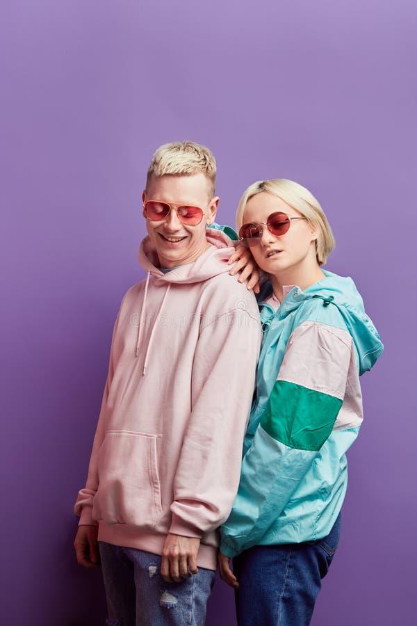 Jeunes couples ? la mode des danseurs posant avec la boule de disco sur le fond violet photos libres de droits