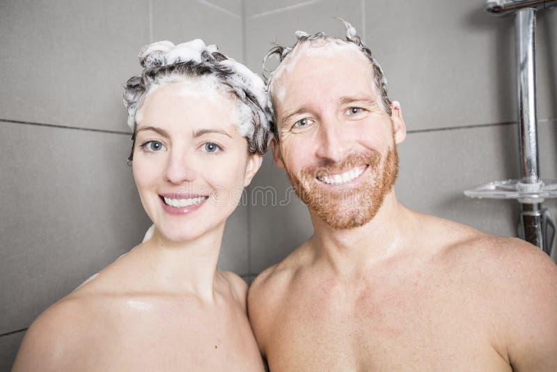 Jeunes couples lavant leurs têtes dans la douche images stock
