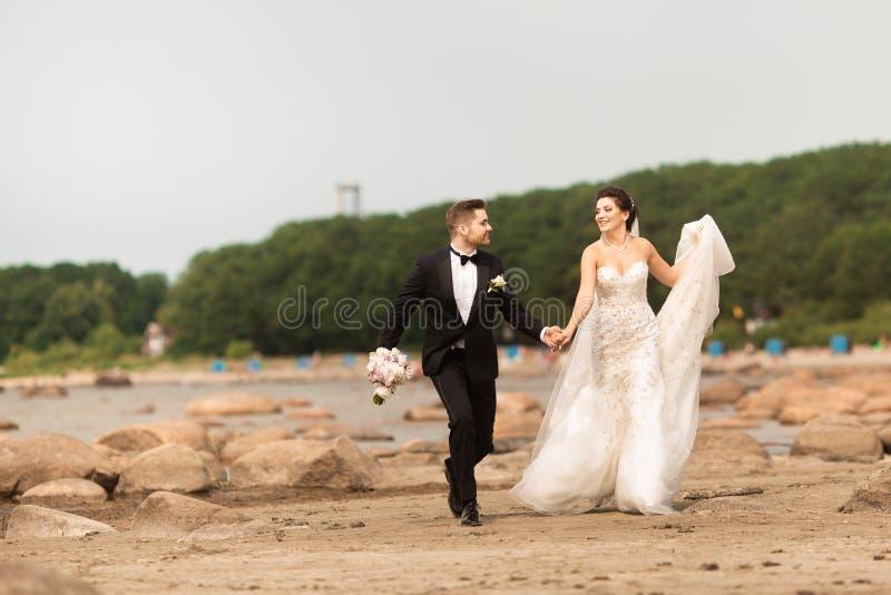 Jeunes couples les épousant heureux ayant l'amusement sur la plage images stock