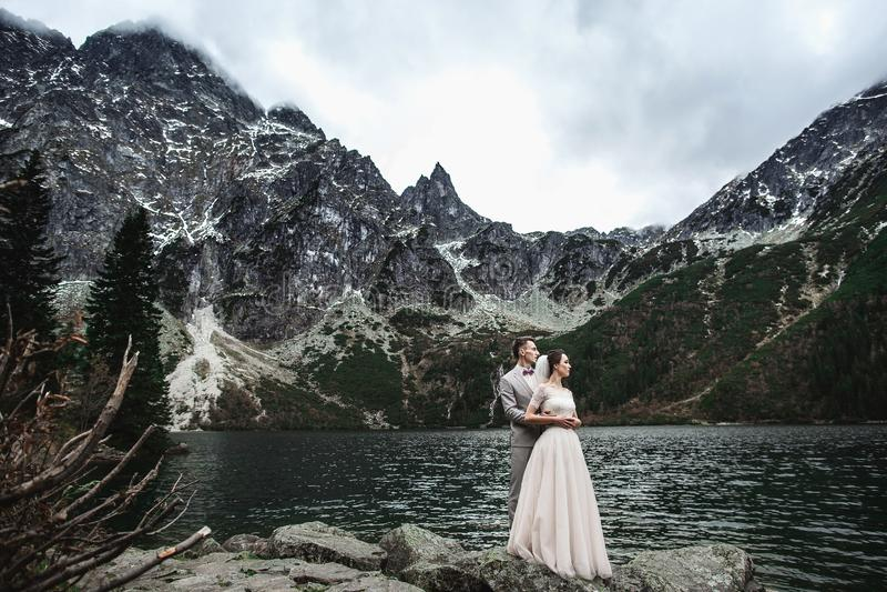Jeunes couples les épousant posant sur le rivage du lac Morskie Oko La Pologne, Tatra photos libres de droits