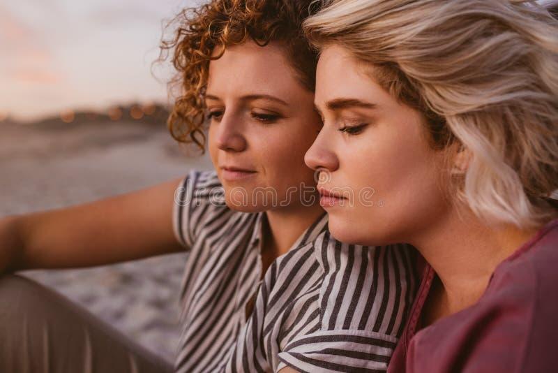 Jeunes couples lesbiens appréciant un coucher du soleil romantique de plage ensemble image stock