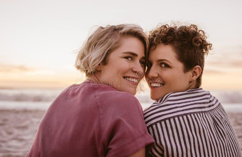 Jeunes couples lesbiens de sourire observant un coucher du soleil romantique de plage photos libres de droits