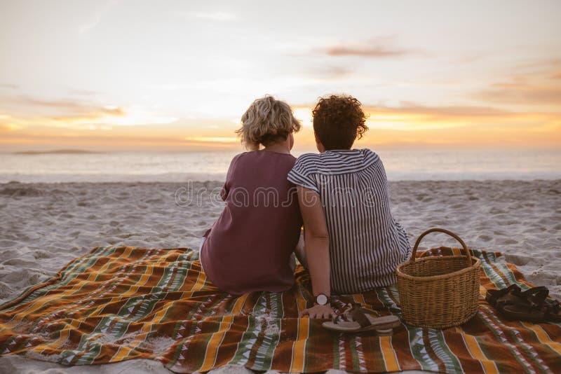Jeunes couples lesbiens observant un coucher du soleil romantique à la plage images libres de droits