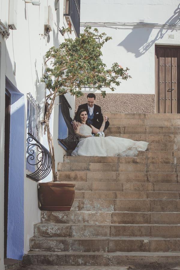 Jeunes couples leur jour du mariage, se reposant sur un grand escalier image stock