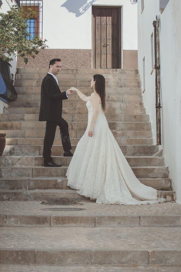 Jeunes couples leur jour du mariage, sur un grand escalier photographie stock libre de droits