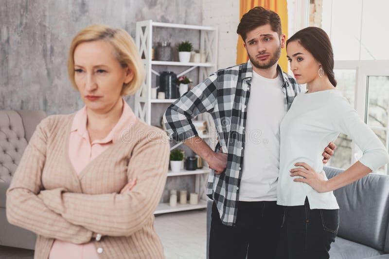 Jeunes couples malheureux regardant la femme âgée images stock