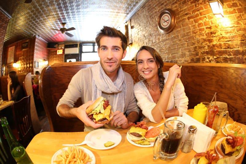 Jeunes couples mangeant des hamburgers dans le restaurant photos libres de droits