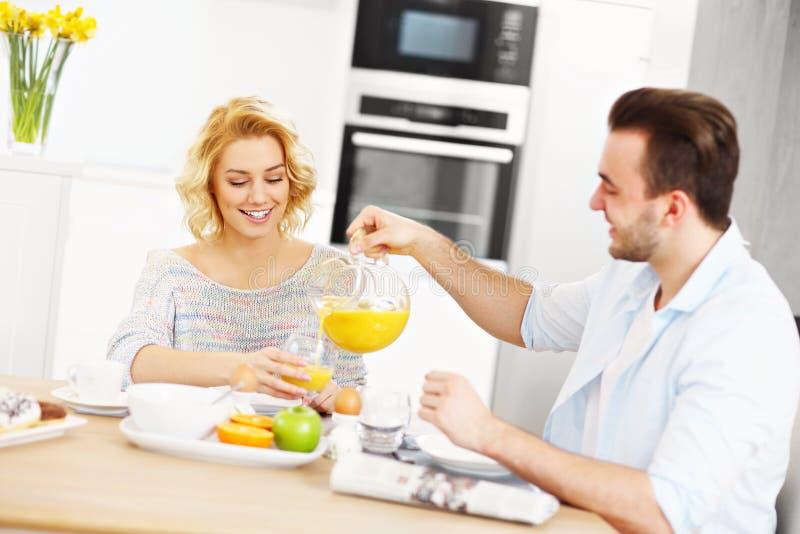 Jeunes couples mangeant le petit déjeuner image stock