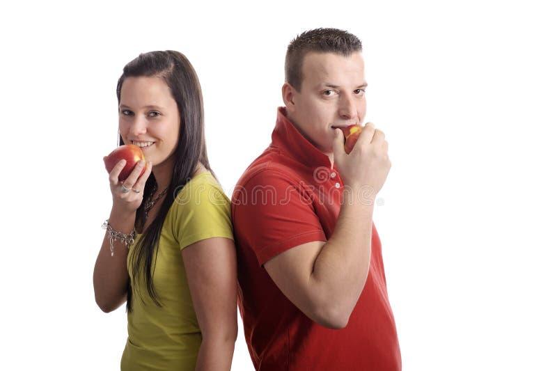 Jeunes couples mangeant une pomme photos stock