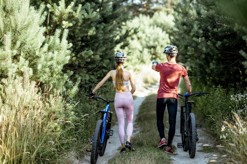 Jeunes couples marchant avec des bicyclettes dehors photos libres de droits