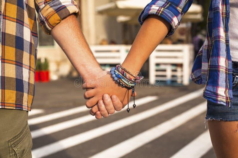 Jeunes couples marchant dans la ville tenant des mains image stock