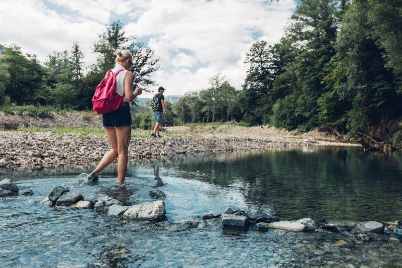 Jeunes couples marchant le long de la côte de la rivière de montagne en été Fille pataugeant à travers la rivière image libre de droits