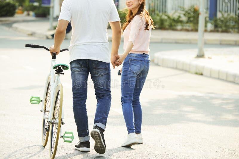 Jeunes couples marchant le long de la rue photos stock