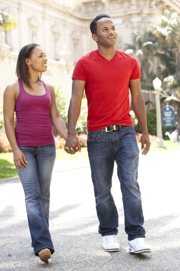 Jeunes couples marchant par la rue de ville photos stock