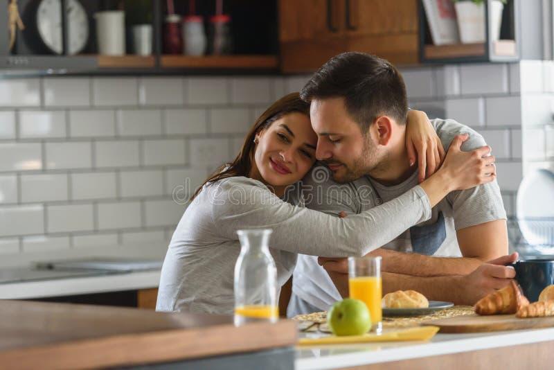 Jeunes couples mariés beaux prenant le petit déjeuner pendant le matin à la maison dans leurs pyjamas photos libres de droits