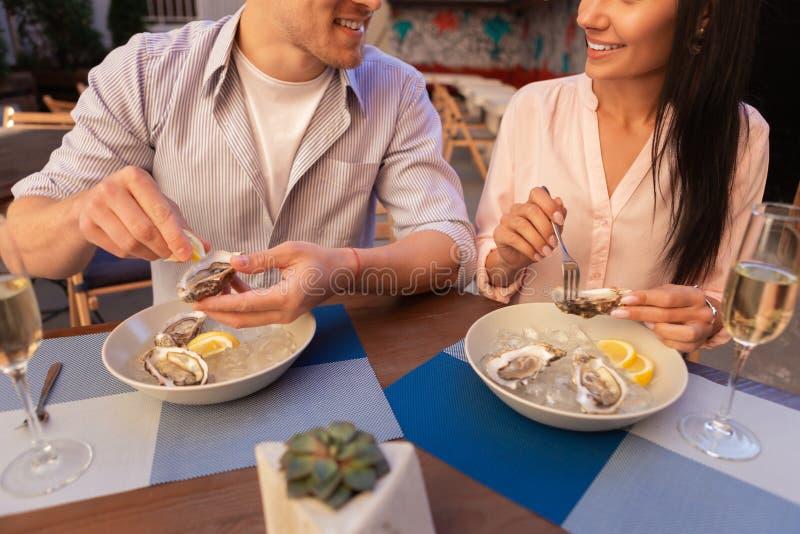 Jeunes couples mignons ayant la date romantique dans le restaurant de fruits de mer photos stock