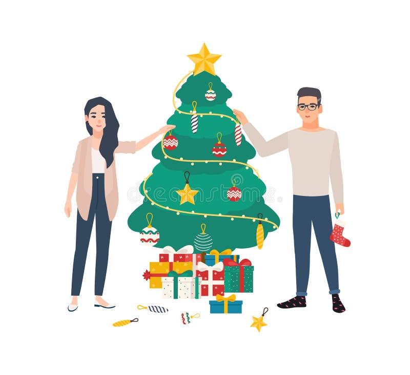 Jeunes couples mignons décorant l'arbre de Noël avec des babioles et des guirlandes légères Homme heureux et femme de sourire se  illustration libre de droits