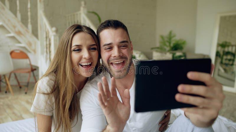 Jeunes couples mignons et affectueux ayant la causerie visuelle tenant la tablette et causant aux parents s'asseyant dans le lit  images libres de droits