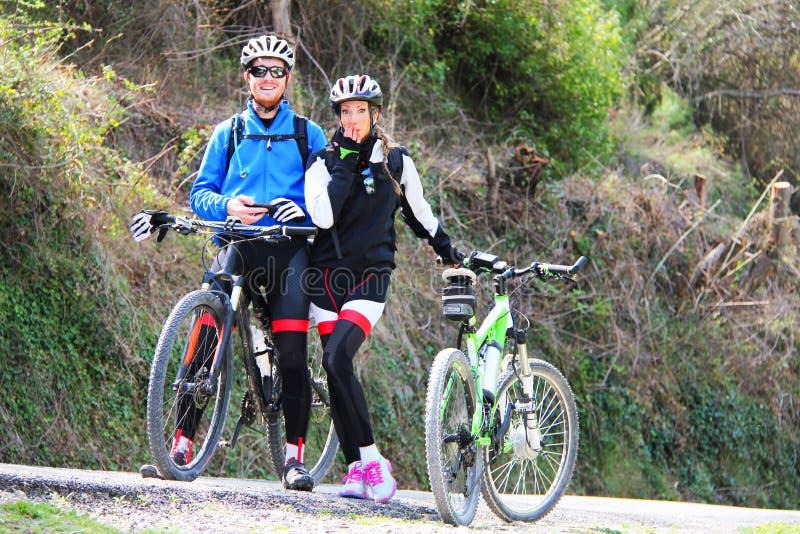 Jeunes couples montant un vélo photographie stock