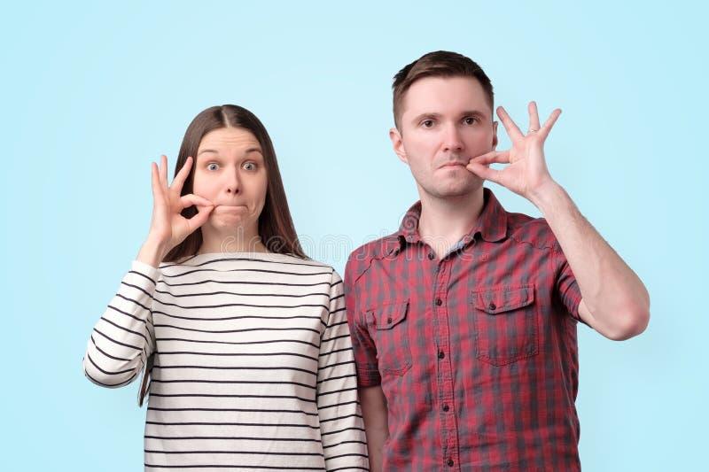 Jeunes couples muets tenant des doigts sur des lèvres comme la tirette pour garder le secret pour la conspiration images stock