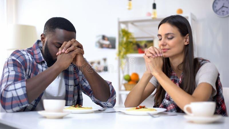 Jeunes couples multi-ethniques priant avant le déjeuner, remerciant Dieu du repas, religion image stock