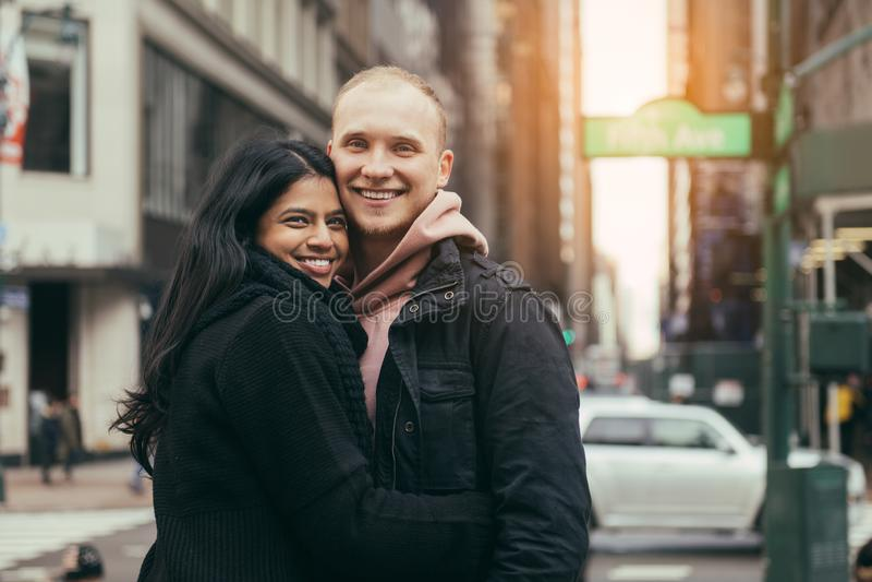Jeunes couples multiculturels adultes heureux dans l'amour étreignant et souriant sur la rue de New York City photos stock