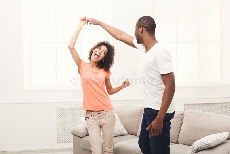 Jeunes couples noirs heureux dansant à la maison, l'espace de copie photos stock