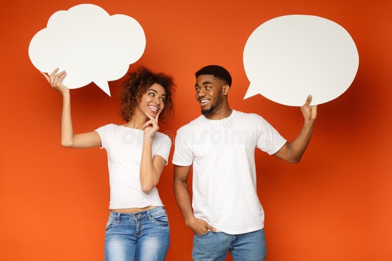 Jeunes couples noirs tenant des bulles de la parole sur le fond orange image stock