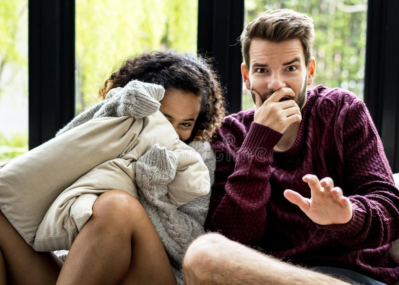 Jeunes couples observant le film effrayant ensemble photographie stock