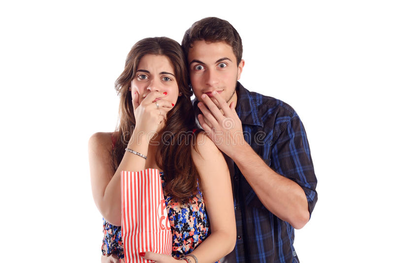 Jeunes couples observant un film effrayant et mangeant du maïs éclaté photos libres de droits
