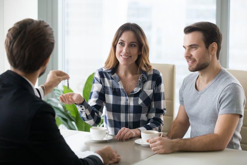 Jeunes couples obtenant des clés au nouvel appartement de l'agent immobilier images libres de droits