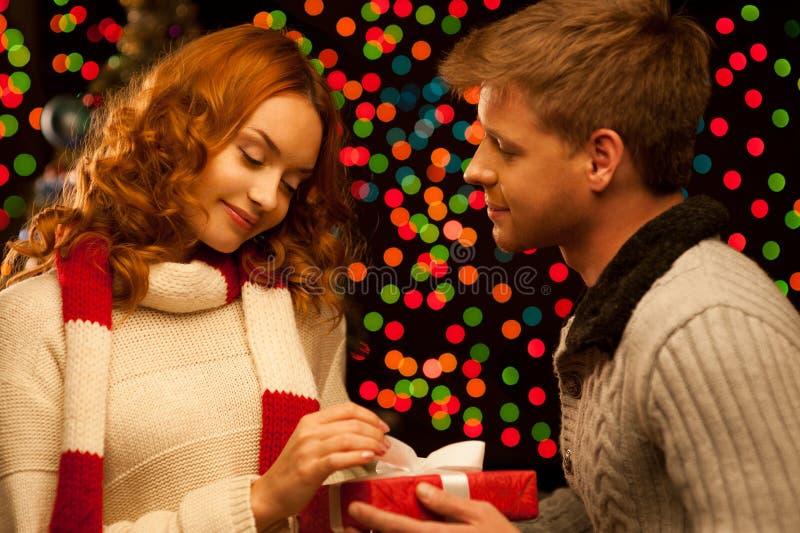 Jeunes couples occasionnels de sourire heureux effectuant un présent photo stock
