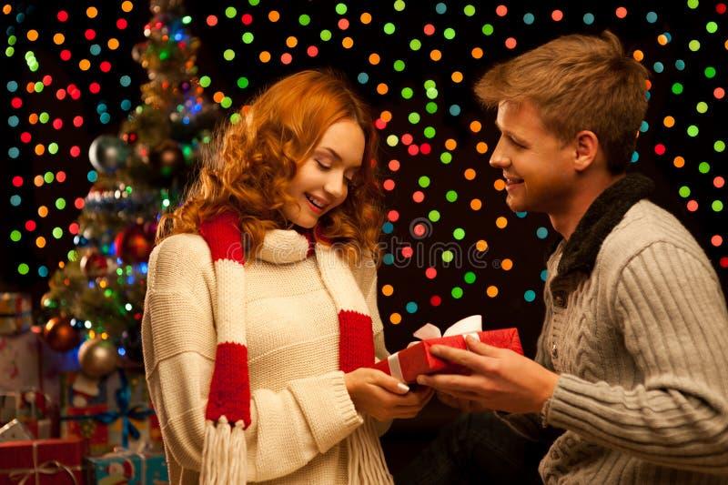 Jeunes couples occasionnels de sourire heureux effectuant un présent photographie stock libre de droits
