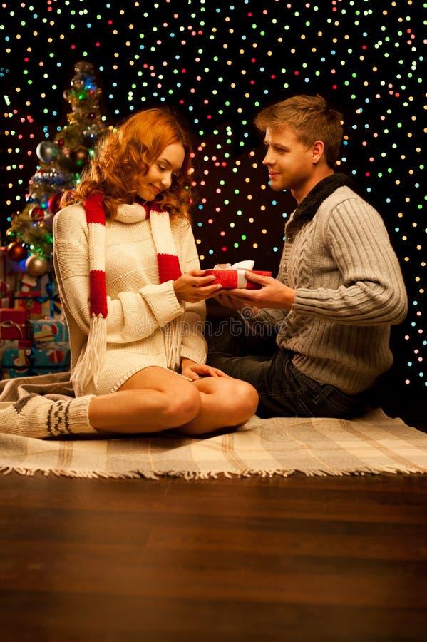 Jeunes couples occasionnels de sourire heureux effectuant un présent images stock