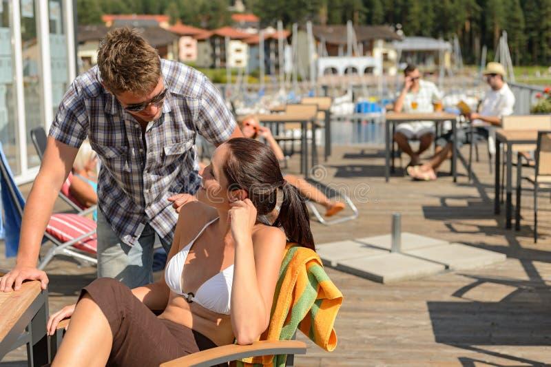 Jeunes couples parlants à la barre de plage photo libre de droits