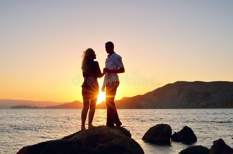 Jeunes couples parlant à une roche par la mer images stock