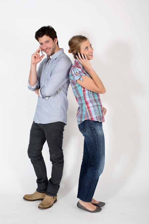 Jeunes couples parlant au téléphone d'isolement photographie stock libre de droits