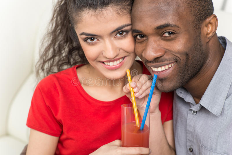 Jeunes couples partageant le verre de jus d'orange et regardant l'appareil-photo images stock