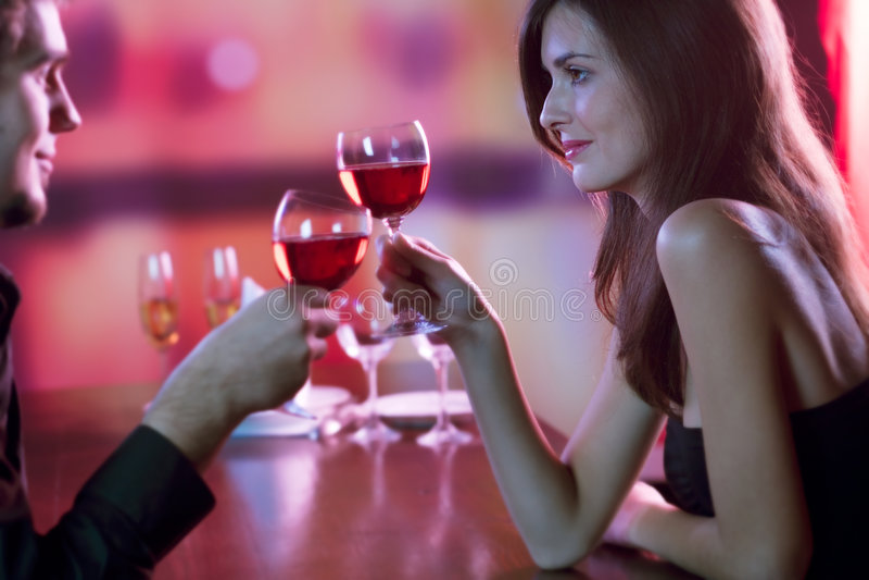 Jeunes couples partageant une glace de vin rouge dans le restaurant, celebrat images stock