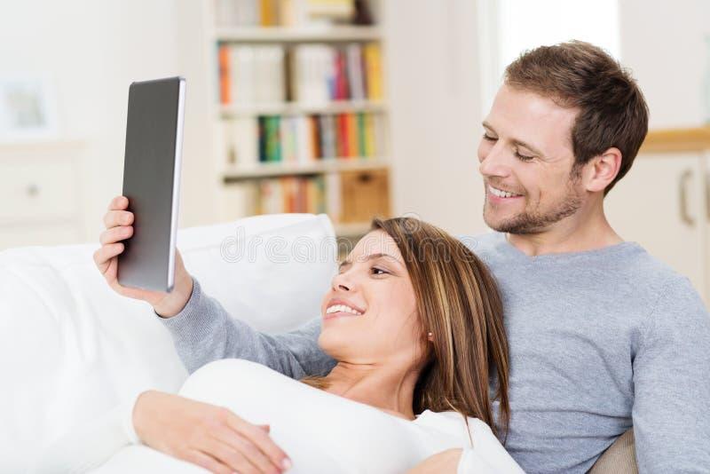 Jeunes couples partageant une tablette images stock