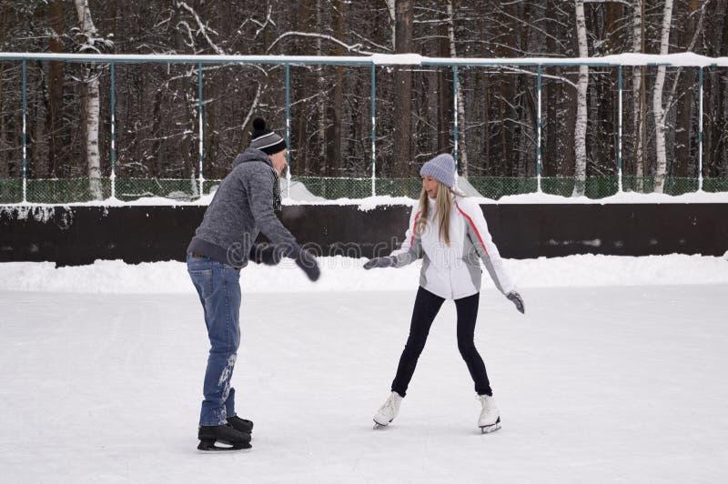 Jeunes couples patinant ? une piste de patinage publique de glace dehors dans la ville image stock