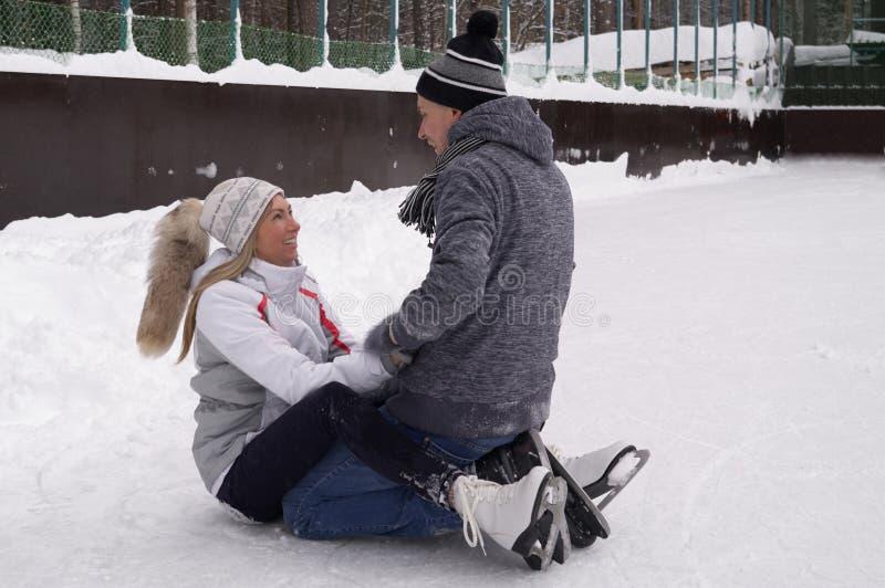 Jeunes couples patinant ? une piste de patinage publique de glace dehors dans la ville images stock