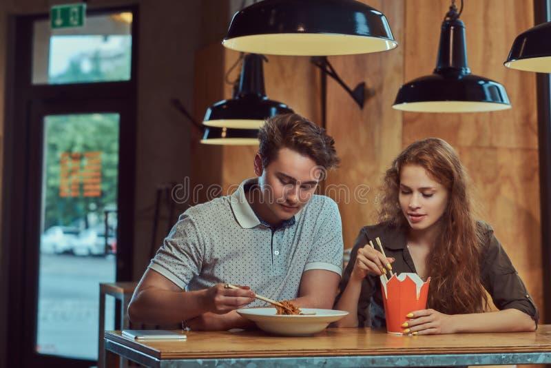 Jeunes couples portant les vêtements sport mangeant les nouilles épicées dans un restaurant asiatique photos stock