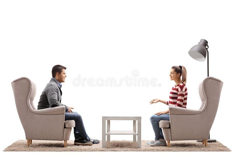 Jeunes couples posés dans des fauteuils ayant une conversation image libre de droits