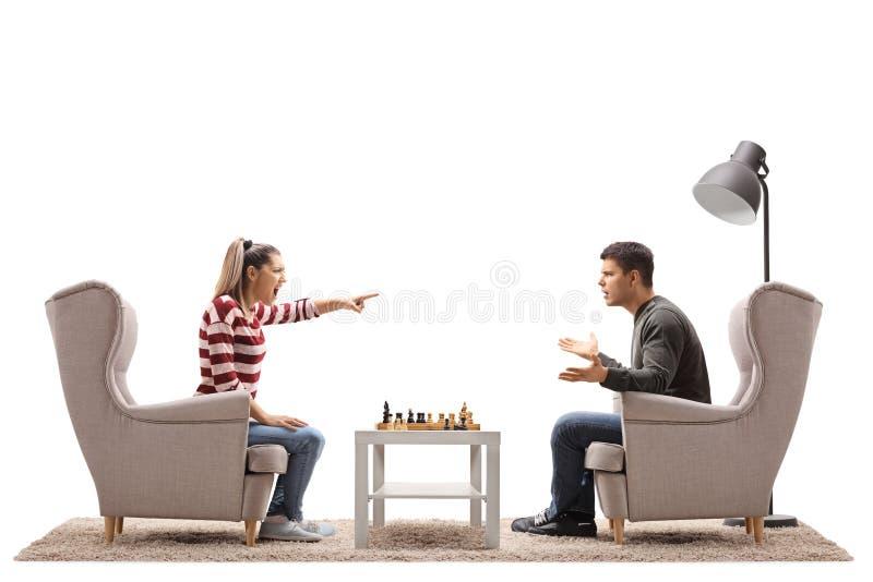 Jeunes couples posés dans des fauteuils jouant des échecs et l'argumentation image libre de droits