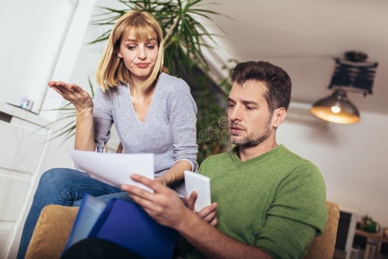 Jeunes couples positifs embrassant et calculant les factures à la maison images libres de droits