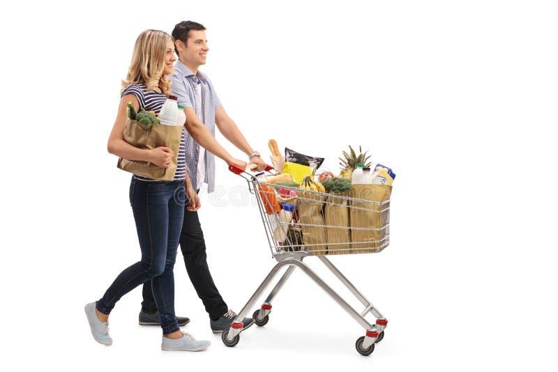 Jeunes couples poussant un caddie photo libre de droits