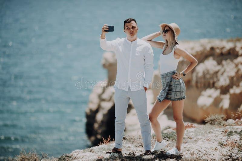 Jeunes couples prenant la photo d'autoportrait de selfie sur le dessus de la falaise sur le fond d'océan Amants, femme heureuse e photo libre de droits