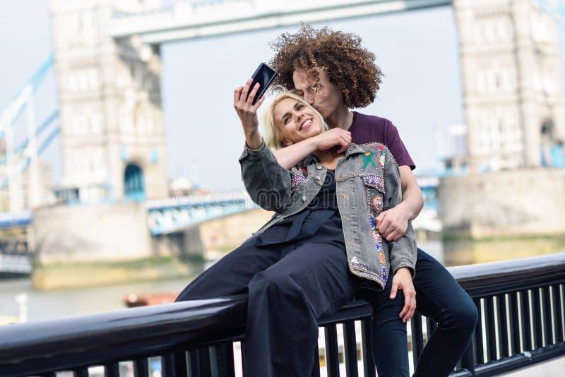 Jeunes couples prenant la photographie de selfie au pont de tour image stock